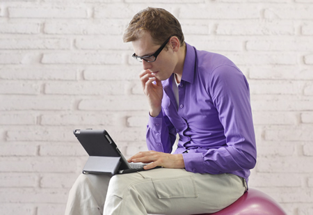 Photo of man hunched over laptop